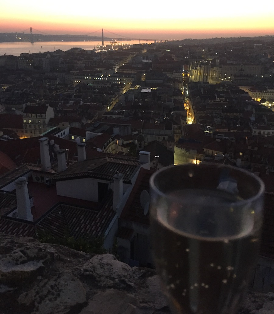 With a glass of wine overlooking St. Jorge's Castle in Lisbon at night